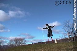 Lisa Bufano standng on tall stilts on a grassy hill, against a deep blue sky with fluffy clouds